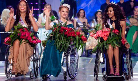 Três mulheres em cadeiras de rodas, uma ao lado da outra, sorrindo e segurando ramos de rosas vermelhas. Ao fundo, várias mulheres em cadeiras de rodas