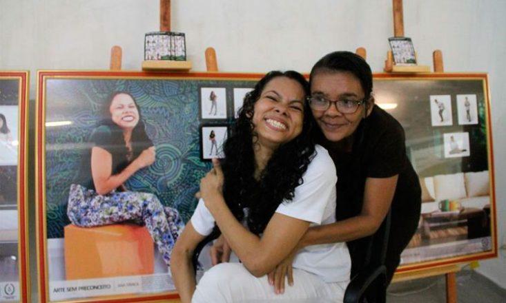 Duas mulheres abraçadas, uma de branco (na frente), rindo, e outro por trás. Ao fundo, várias fotografias da primeira mulher