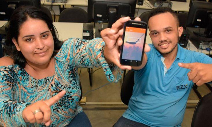 Uma mulher (à esquerda) e um homem, sentados, seguram um celular e apontam para a tela