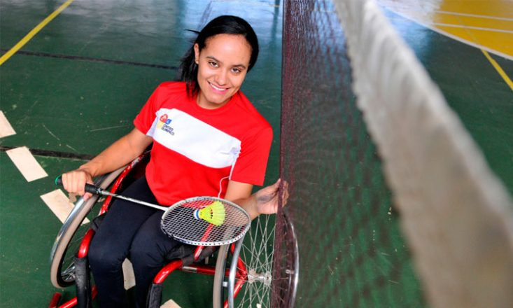 Mulher em uma cadeira de rodas, segura uma raquete e peteca de badminton, em uma quadra da modalidade