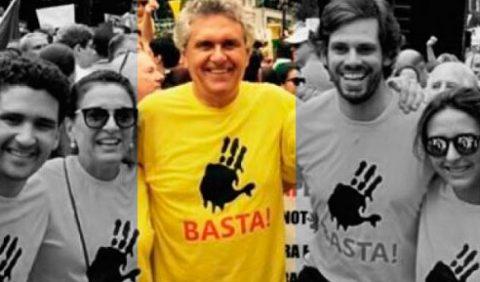 Foto em uma manifestação, em preto e branco, com um homem ao centro, em cores, todos com uma camisa amarela, um desenho preto de uma mão com quatro dedos no peito e a palavra BASTA!, em vermelho, embaixo