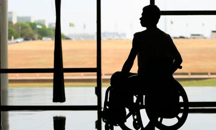 Foto horizontal de um homem em uma cadeira de rodas, em primeiro plano, em tom escuro, e, ao fundo, uma área externa com jardim, ruas, carros e bandeiras