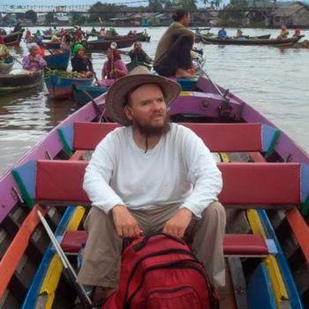 Voto quadrada de um homem em um barco, com uma mochila vermelha a sua frente. Ao fundo, vários outros barcos e pessoas navegando