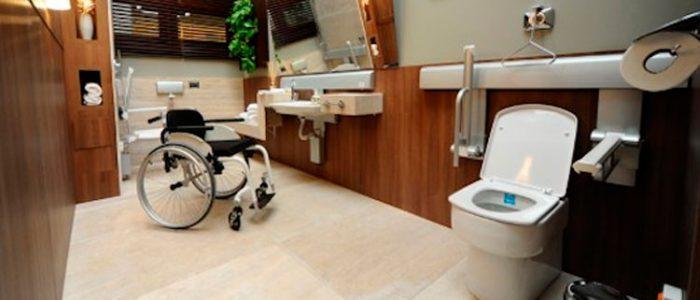 Banheiro adaptado com uma cadeira de rodas ao centro
