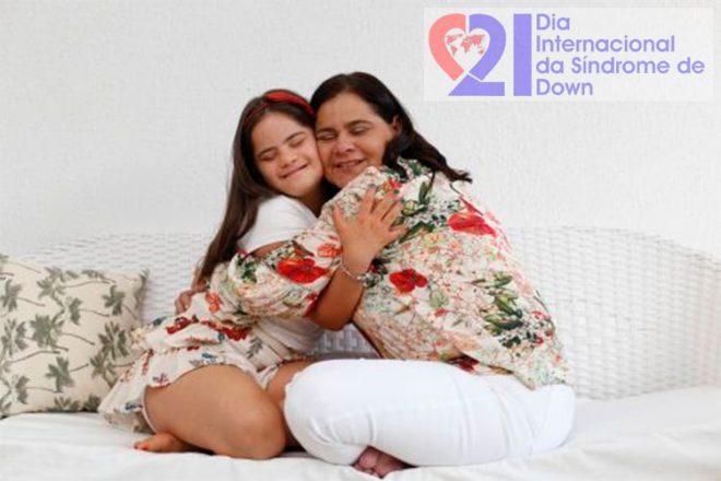 Uma mulher abraçada a sua filha adolescente e com Síndrome de Down, ambas sentadas em um sofá. No alto, à direita, a logomarca do Dia Internacional da Síndrome de Down.