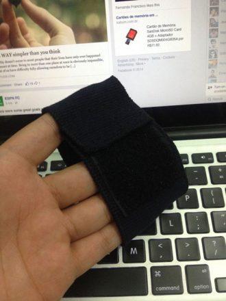 Foto vertical de uma mão segurando uma pequena pulseira preta. Ao fundo, a tela de um laptop