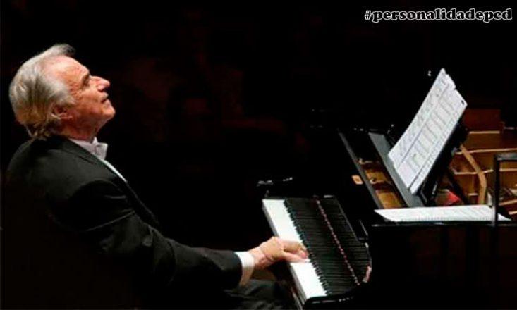 Foto horizontal, escura, de um homem de meia idade, vestindo um fraque preto, de lado, tocando piano. No alto, à direita, o sinal de hashtag e as palavras personalidadepcd