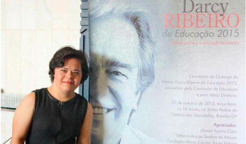 Foto horizontal de uma mulher jovem no canto esquerdo, sorrindo, a frente de um cartaz grande com o rosto do educador Darcy Ribeiro