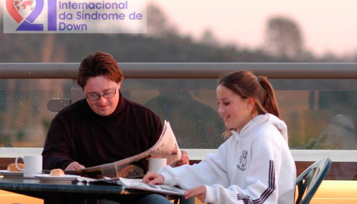 Um casal, ele com Síndrome de Down, sentado em uma mesa, tomando café, lendo jornal e com montanhas ao fundo. No alto, à esquerda, a logomarca do Dia Internacional da Síndrome de Down.