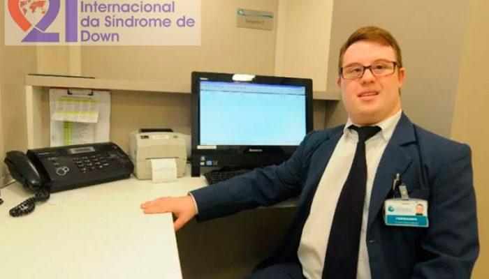 Um jovem de paletó e gravata, com Síndrome de Down, em um escritório, com um computador e um aparelho de fax a sua frente. No alto, à esquerda, a logomarca do Dia Internacional da Síndrome de Down.