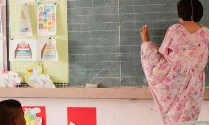 Sala de aula com uma professora, à direita, escrevendo no quadro com o pé esquerdo. No canto inferior esquerdo, a cabeça de um aluno. Ao lado do quadro, papéis afixados num mural, com desenhos de bichinhos