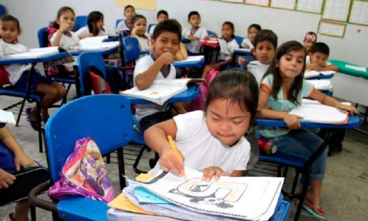 Sala de aula infantil com dezesseis crianças sentadas em suas carteiras, uniformizadas, lendo. Em primeiro plano, uma garotinha com Síndrome de Down pinta um número 5 bem grande
