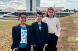 #pracegover: Três jovens (dois meninos e uma menina), de pé, sorrindo, e, ao fundo, o Congresso Nacional