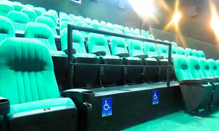 #pracegover: Sala de cinema bastante iluminada, visto de baixo para cima, com diversos assentos e tapete verdes. No centro, um espaço vazio para receber duas cadeiras de rodas.
