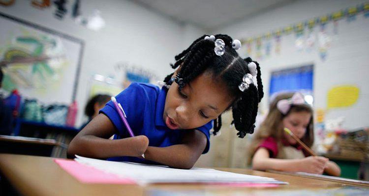 Foto horizontal de uma sala de aula com duas garotinhas na imagem. A da esquerda, em destaque, é uma garota negra, com roupa azul, segurando um lápis com a mão direita e apoiando o papel com o cotovelo esquerdo. Ela não tem as mãos. Ao fundo, desfocado, há vários desenhos e outros objetos pendurados nas paredes.
