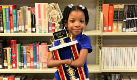 Foto horizontal de uma garotinha negra ao centro, segurando um troféu entre os braços, sorrindo. Ela não possui as mãos e, atrás dela, uma estante com vários livros.