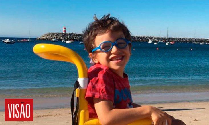 Foto horizontal na praia com a foto, em close, de um garotinho de perfil, sorrindo, em uma cadeira de rodas amarela. Ao fundo, o mar, barcos e um farol. No canto inferior esquerdo, a palavra VISÃO em letras brancas dentro de um quadrado vermelho.