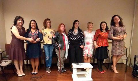 Foto horizontal de oito mulheres, lado a lado, de mãos dadas, em um palco. Atrás delas, oito cadeiras. À frente, um banquinho branco com dois microfones em cima.