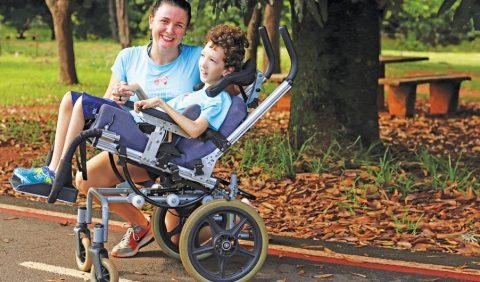 Foto horizontal em um parque de uma mãe acocorada ao lado de seu filho em uma cadeira de rodas. Ao fundo, uma árvore, plantas e bancas.