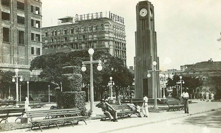 Foto em preto e branco da Praça do Ferreira, com a torre do relógio à direita, prédios ao fundo, vários bancos e pessoas caminhando ou sentadas
