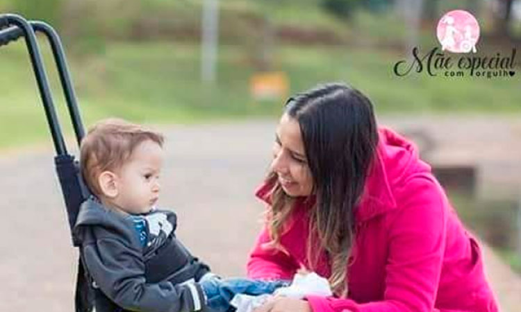 Mãe ajoelhada, sorrindo para o filho a sua frente, sentado em uma cadeirinha de criança, em um parque. No alto, à direita, a logo do blog Mãe Especial com Orgulho.