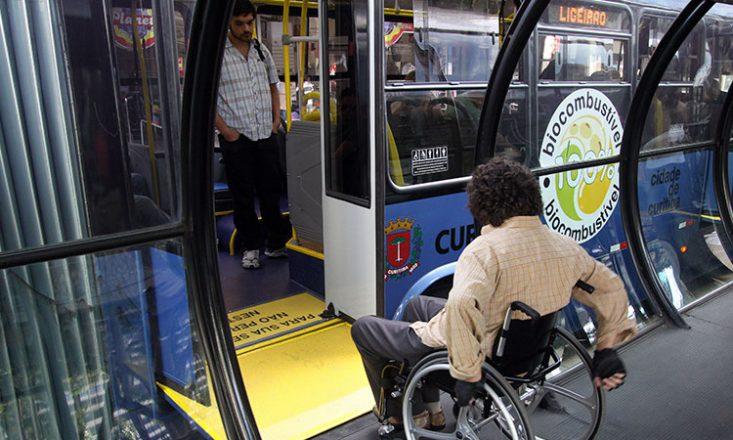 Homem em uma cadeira de rodas entra em um metrô da prefeitura de Curitiba, utilizando uma rampa amarela na porta. Na lateral do veículo, lê-se a placa redonda: 100% biocombustível.