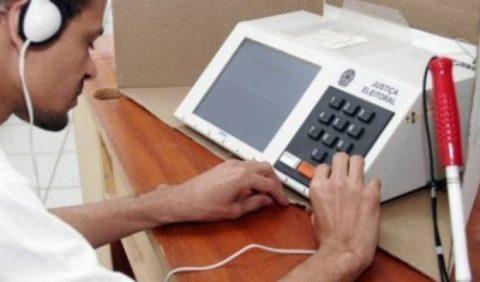 Pessoa com deficiência visual votando com tecnologia assistiva de fone de ouvido nas urnas eleitorais.