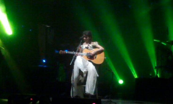 Foto horizontal de Nathalie em um palco, sentada em um banco alto, tocando um violão e várias luzes esverdeadas a iluminando