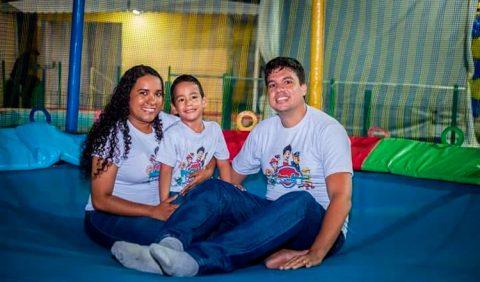 Foto horizontal em um brinquedo de pula pula, com três pessoas: um casal e um garotinho sentado no colo da mãe, entre os dois.