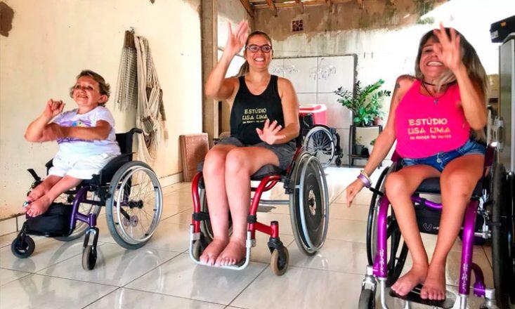 Foto horizontal de três mulheres, uma ao lado da outra, em cadeiras de rodas, ensaiando movimentos de dança