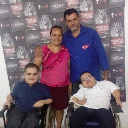 Foto quadrada de uma família. De pé, atrás, uma mulher com uma blusa cor de rosa abraçada a um homem vestido de azul. Em primeiro plano, dois adolescentes em cadeiras de rodas.