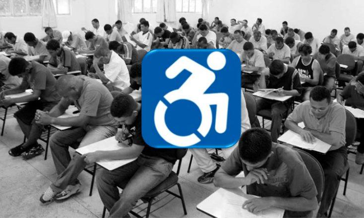 Foto horizontal em preto e branco de uma sala de concurso, com diversas pessoas sentadas, fazendo prova, e, ao centro, o símbolo internacional da pessoa com deficiência, um quadrado azul com um cadeirante em branco ao centro