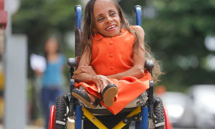 Foto horizontal de uma mulher de 51 anos, na rua, em uma cadeira de rodas, usando um vestido laranja