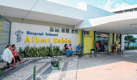 Foto horizontal da entrada do Hospital Infantil Albert Sabin, com nove pessoas esperando atendimento