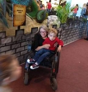 Foto vertical de uma mulher em uma cadeira de rodas com seu filho no colo. Ambos estão em um shopping, na frente de uma estátua de um dragão. Ao fundo, algumas pessoas observam a exposição