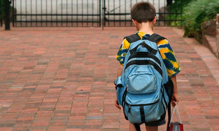 Imagem horizontal de um garotinho de costas, com uma mochila azul, caminhando, de cabeça baixa, sobre um chão de pedras vermelhas, em direção a um portão.