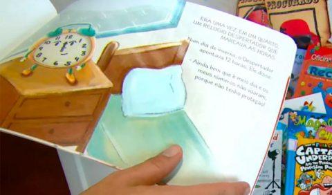 Uma mão, na parte de baixo da imagem, folheia um livro infantil, com o desenho de um relógio à esquerda, sobre um criado-mudo, uma cama de solteiro vazia e, sobre ela, o texto do livro. Ao fundo, vários outros livros e revistas
