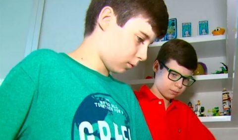Dois irmãos gêmeos, de 10 anos, autistas, lado a lado. Em primeiro plano, Giuliano, de camisa verde; em segundo plano, Luigi, de camisa vermelha e óculos. Ao fundo, uma estante com cartões e brinquedos.