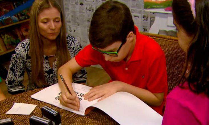 Um garoto autista de 10 anos, ao centro, assina um livro escrito por ele. Ao seu lado, sua mãe o observa e orienta. Do outro lado, uma garotinha o aguarda