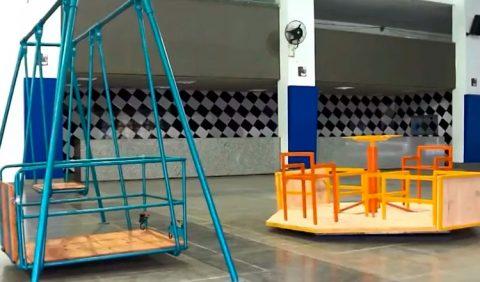 Foto de um ginásio escolar com dois brinquedos adaptados para crianças cadeirantes