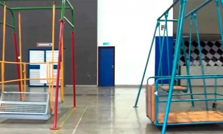 Foto de um ginásio escolar com dois brinquedos adaptados para crianças cadeirantes.