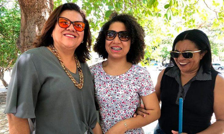 Foto horizontal de três mulheres cegas, uma ao lado da outra, sorrindo. Da esquerda para a direita: Dilma Andrade, Denise Santos e Teresinha Nascimento. Ao fundo, uma árvore e carros.
