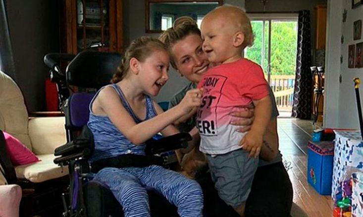 Garotinha com paralisia cerebral, em uma cadeira de rodas, brinca com seu irmãozinho de um ano de idade e a mãe, na sala da sua casa.