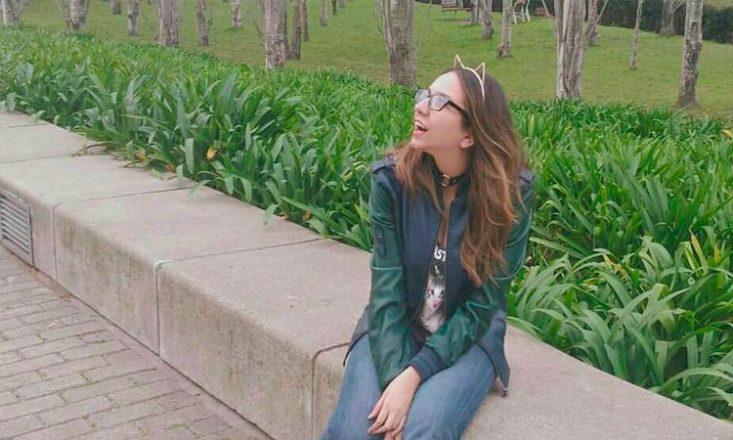 Garota com Síndrome de Asperger sentada em um batente de jardim, olhando para o alto, sorrindo. Ao fundo, muitas plantas e árvores