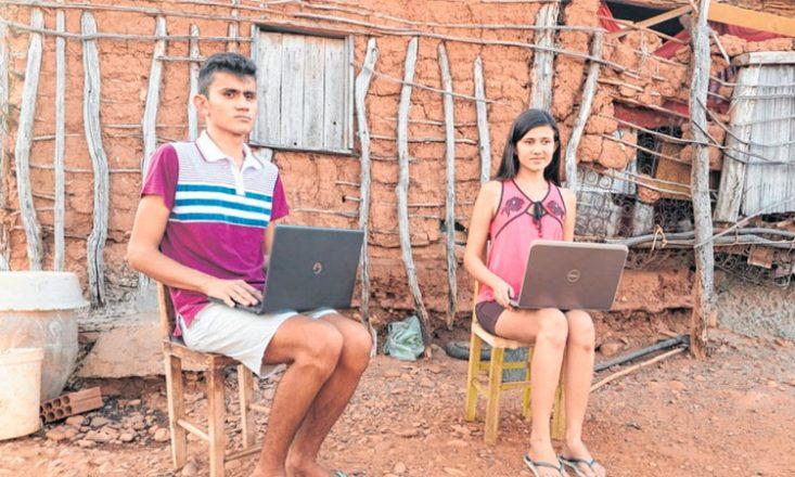 Dois irmãos, um rapaz (à esquerda) e uma moça, sentados em cadeiras de madeira, com um laptop no colo, no terreiro de uma casa bastante humilde