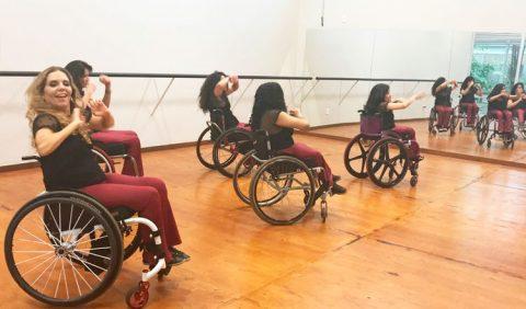 Cinco moças cadeirantes ensaiam uma dança em um salão, de frente a um espelho.