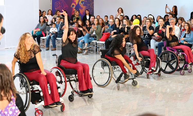 Cinco moças cadeirantes dançam em uma apresentação cultural para uma platéia composta de homens e mulheres ao seu redor.