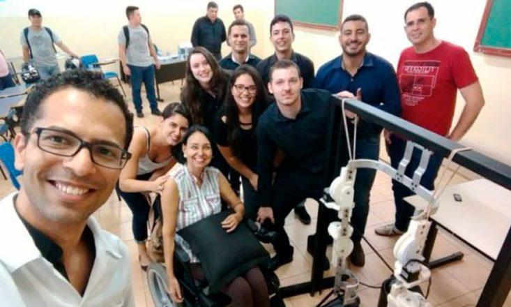 Uma mulher em uma cadeira de rodas, de frente para um aparelho mecânico, e cercada por nove pessoas sorrindo para a câmera. Ao fundo da sala, cinco outras pessoas de pé.