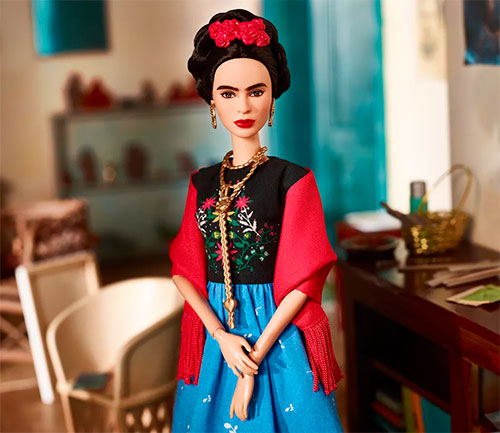 Boneca Barbie vestida de Frida Khalo, com uma saia azul, blusa preta com estampa de flores, um cordão longo e dourado no pescoço, uma flor vermelha nos cabelos e brincos dourados. Ao fundo, uma mesa com pincéis e uma cesta, uma cadeira branca e uma estante