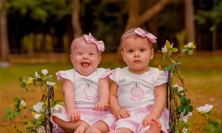 Duas bebês gêmeas, sentadas em uma cadeira de ferro no jardim, usando vestidos cor de rosa com o desenho de uma maçã no peito e laços cor de rosa na cabeça. A bebê da esquerda, Luísa, tem Síndrome de Down; a outra, Lívia, não.